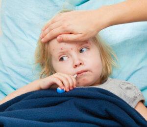 Заболевание сопровождается повышенной температурой, болью в горле и сыпью